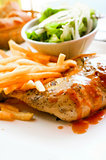 Chicken with sauce and golden French fries