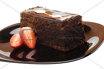 A piece of chocolate cake on a plate with strawberries