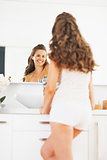Happy young woman looking in mirror in bathroom