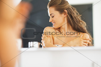 Portrait of young woman in bathroom happy with her skin conditio