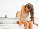 Frustrated young woman sitting in bathroom