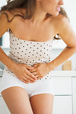 Closeup on woman having stomachache in bathroom