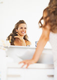 Happy woman looking in mirror in bathroom