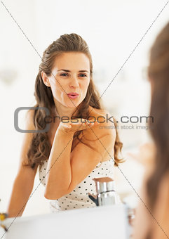 Happy young woman blowing air kiss in mirror in bathroom
