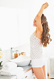 Young woman in bathroom stretching after sleep