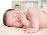 Asian baby girl biting fingers