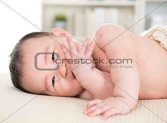Asian baby girl biting fingers