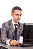 Young businessman sitting at office desk working with laptop