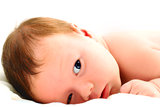 Portrait of a baby lying on white.