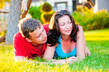 Young couple lying on the grass, and that it is considering
