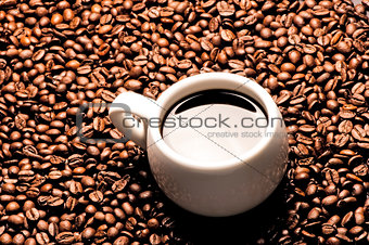 A cup of coffee on a background coffee grains