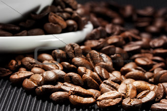 Coffee beans scattered on a black grooved