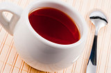 White cup with fresh tea on wooden mat.