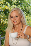 Mature attractive woman drinking coffee outdoors