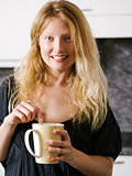 Blond female enjoying coffee at home