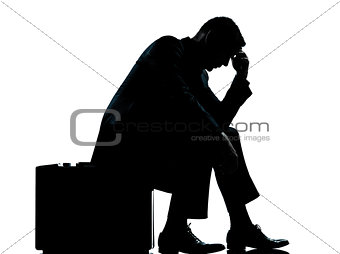 one business man sitting on suitcase tired despair silhouette
