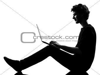 young man silhouette sitting computing laptop