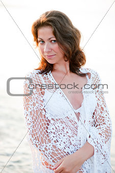 Portrait of a beautiful girl in a white shawl on the beach.