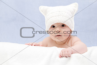 Beautiful baby in white hat lies on bed