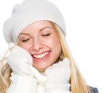 Smiling girl in winter clothes enjoying soft scarf