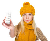 Serious girl in scarf and hat showing blister package of pills
