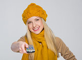 Happy girl in scarf and hat with tv remote control isolated on g