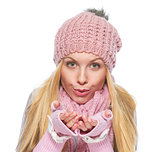 Girl in winter clothes blowing snow from hands