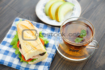 Breakfast with sandwich, tea and melon
