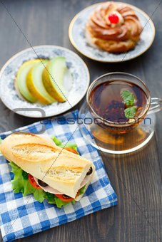 Breakfast with sandwich, tea, cake and melon