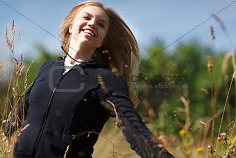 Young happy girl running in the field