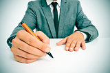 man in suit with a pen in his hand ready to write