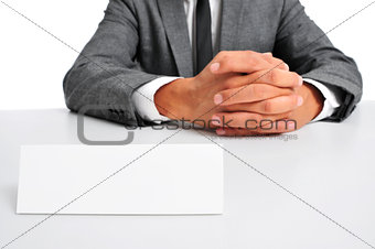 man in suit sitting in a desk with a blank signboard in front of
