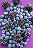 Blackberries and blueberries on a purple background