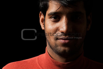 Portrait of young Indian man over dark