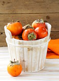 Orange ripe persimmon in a wooden table