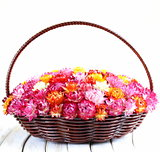 wicker basket with multicolored flowers on wooden table
