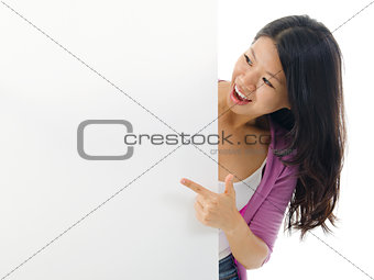 Asian woman pointing to blank billboard.