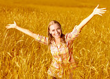 Cheerful girl on wheat field