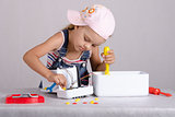 Girl repairs toy small home appliances