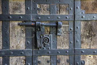 Ancient iron lock with latch on aged boarded door.