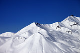 Snowy winter mountains and clear blue sky in sun day