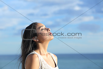 Beautiful arab woman breathing fresh air in the beach