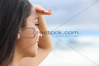 Close up of a beautiful woman looking at the horizon with a hand in forehead
