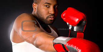 African American Male Puncher Hits Heavy Bag with Red Boxing Gloves