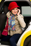 Woman Prepared for Winter exits a Taxi Talking on Cell Phone