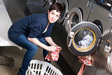 Serious Woman Does Chores Folding Clothes in the Laundromat