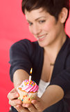 Bright Confident Female Holds Celebration Cupcake Out to Blow Candle