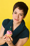 Pretty Woman Holds Birthday Cupcake One Candle Yellow Background