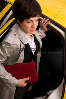 Attractive Business Woman Enters a Yellow Taxi Cab