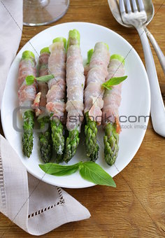 appetizer of fried asparagus with ham and basil